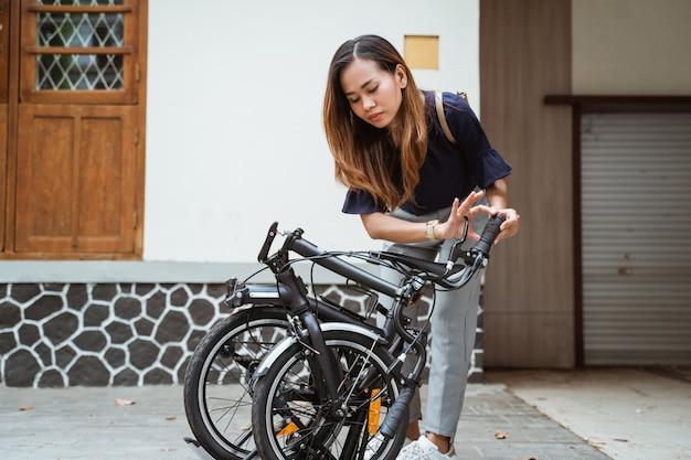 Asiatique jeune femme essayant de plier son vélo pliant pour se préparer à aller travailler