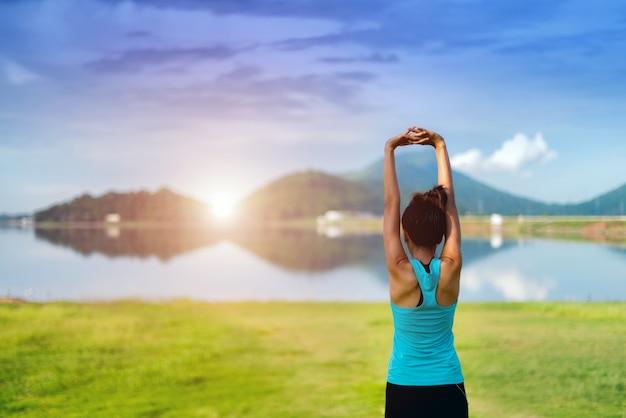 Asiatique jeune femme exerçant sur la plage le matin au lever du soleil