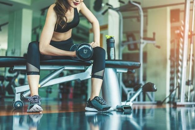 Asiatique jeune femme jouant des exercices d'haltères exercice dans la salle de fitness