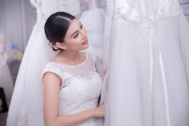 Asiatique jeune femme mariée essayant de robe de mariée au mariage moderne