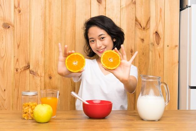 Asiatique jeune femme prenant son petit déjeuner en tenant une orange