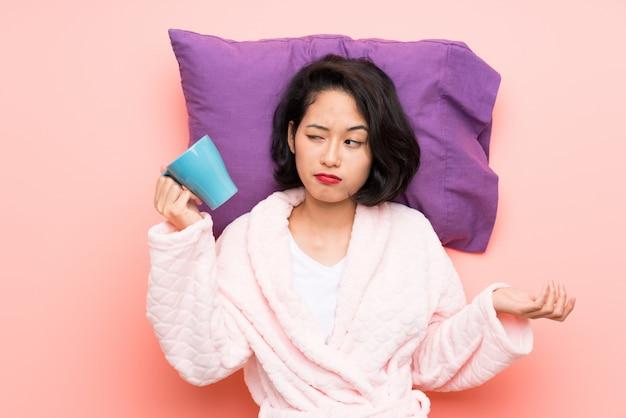 Asiatique jeune femme en pyjama tenant une tasse de café