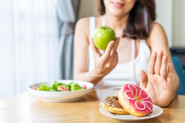 Asiatique jeune femme refuse la malbouffe tout en choisissant de manger une salade saine et des fruits pour sa santé.