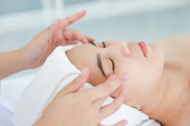 Asiatique jeune femme se cure thermale au salon de beauté. massage du visage au spa. traitement de beauté du visage