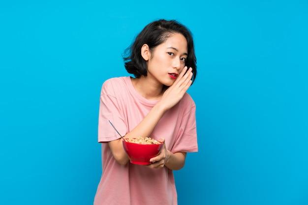 Asiatique jeune femme tenant un bol de céréales murmurant quelque chose