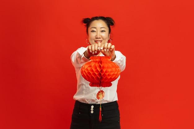 Asiatique, Jeune Femme, Tenue, Lanterne, Sur, Mur Rouge Photo gratuit