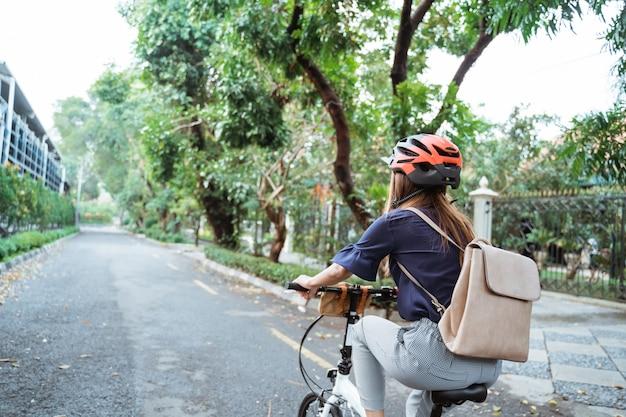 Asiatique jeune femme va porter un casque et un sac sur son vélo pliant
