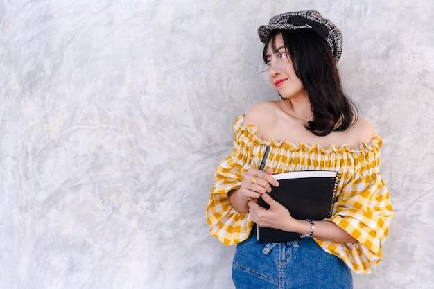 Asiatique jeune fille étudiant positif attrayant sur fond de mur