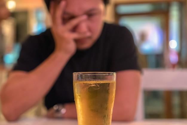 Asiatique jeune homme en action solitaire et déprimée et tenant le visage dans les mains et voir le verre