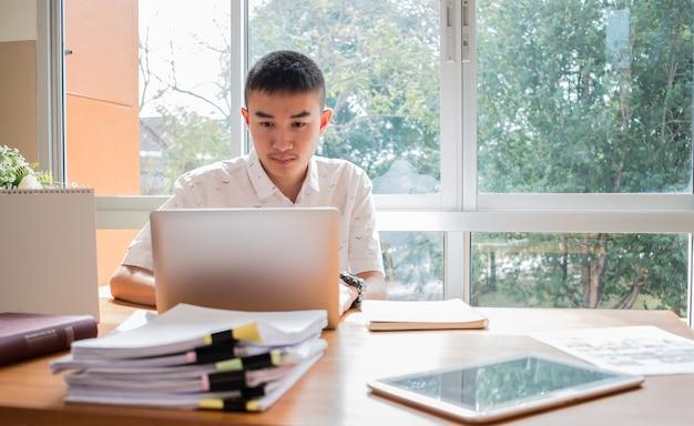 Asiatique jeune homme étudiant apprendre et vérifier les horaires pour projeté dans un ordinateur portable