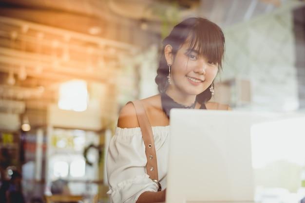 Asiatique jeune et jolie femelle sourire et utiliser un ordinateur portable dans le café