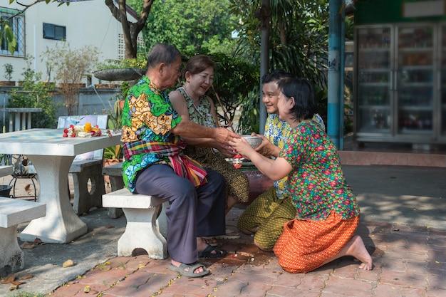 Asiatique jeune se baignant par rapport aux parents par l'eau au festival de songkran