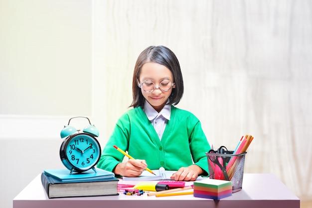 Asiatique jolie fille à lunettes d'apprentissage avec l'école stationnaire sur le bureau