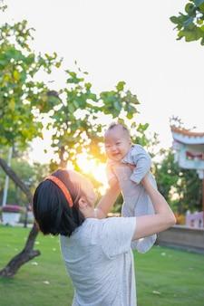 Asiatique mère jette bébé, rire et jouer dans le parc