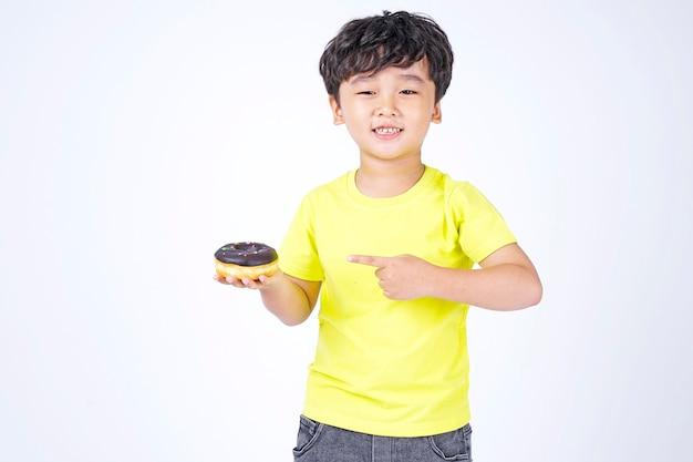Asiatique petit garçon mignon manger gros beignet isolé sur blanc
