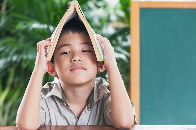 Asiatique petit garçon tenant le livre sur la tête, le concept de l'éducation