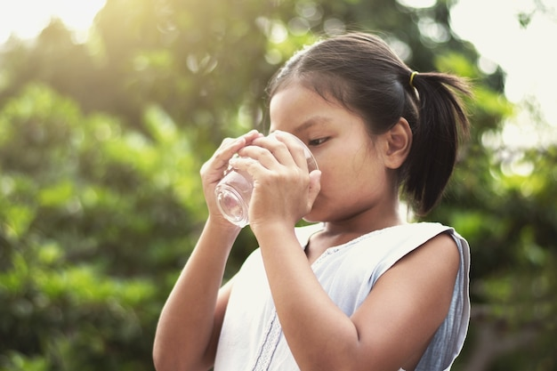 Asiatique petite fille boire de l'eau de verre avec fond de soleil