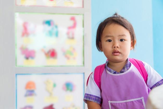 Asiatique petite fille étudiante en uniforme et sac rouge va à l'école