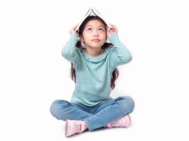 Asiatique petite fille mignonne de 6 ans assise sur le sol et a mis le livre sur la tête. joli enfant d'âge préscolaire avec la couverture du livre sur la tête.