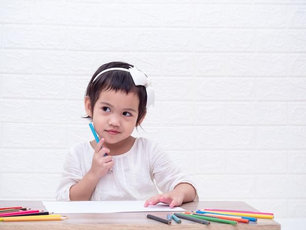 Asiatique petite fille mignonne tenant un crayon