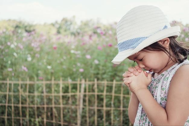 Asiatique petite fille priant, concept de foi de christianisme