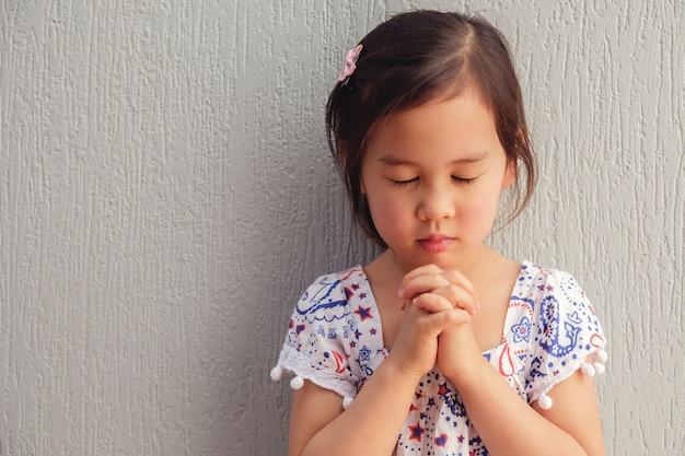 Asiatique petite fille priant avec les yeux fermés