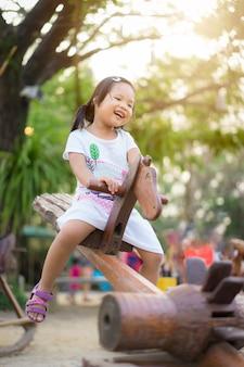 Asiatique petite fille s'amuser sur la bascule au terrain de jeux