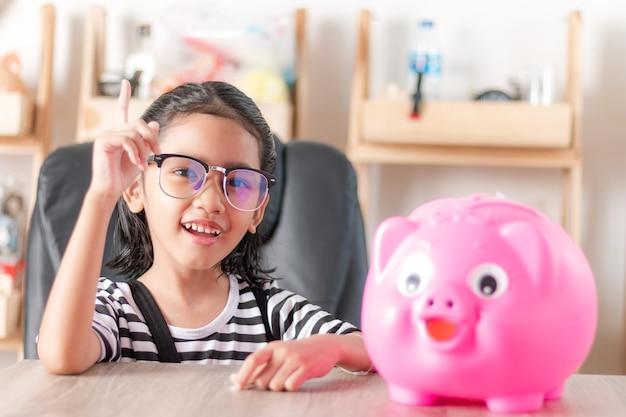 Asiatique petite fille souriante avec tirelire faible profondeur de champ select focus à la face