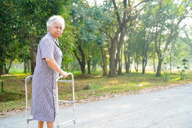 Asiatique senior ou âgée vieille dame patiente marche avec walker dans le parc