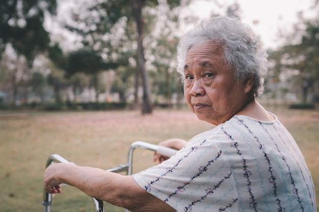 Asiatique senior ou âgée vieille dame patiente à pied avec marcheur dans le parc avec espace de copie, concept médical fort sain