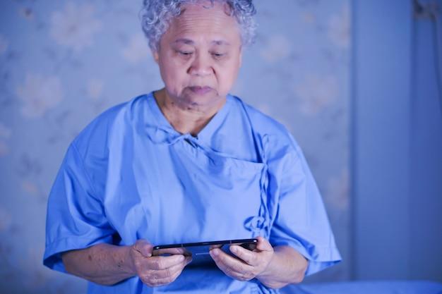 Asiatique senior âgée vieille dame patiente tenant dans la main une tablette numérique lire email.