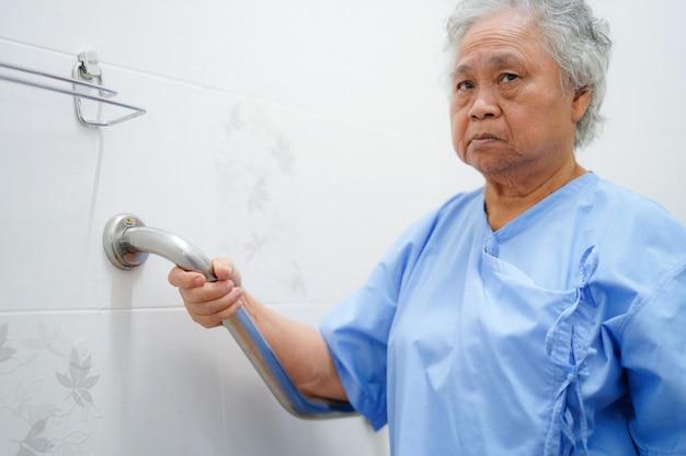 Asiatique senior ou âgée vieille dame patiente utiliser sécurité de poignée de toilette dans un hôpital de soins infirmiers.