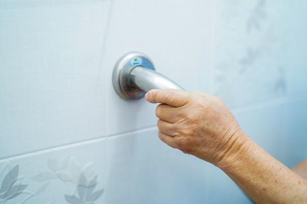 Asiatique senior ou âgée vieille dame patiente utiliser la sécurité de la poignée de toilette dans un hospi
