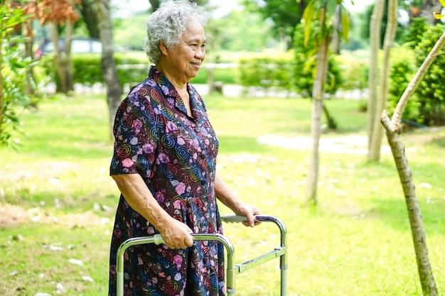 Asiatique senior ou âgée vieille femme patiente à pied avec walker dans le parc.