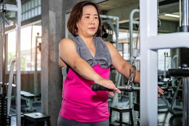 Asiatique senior fat woman in sportswear training arm with machine at gym.