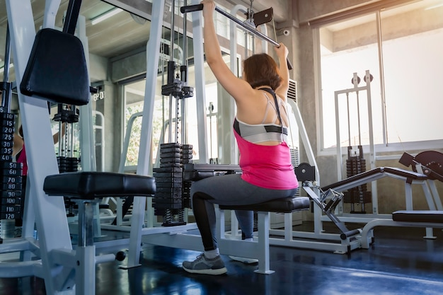 Asiatique senior fat woman in sportswear training back with machine at gym.