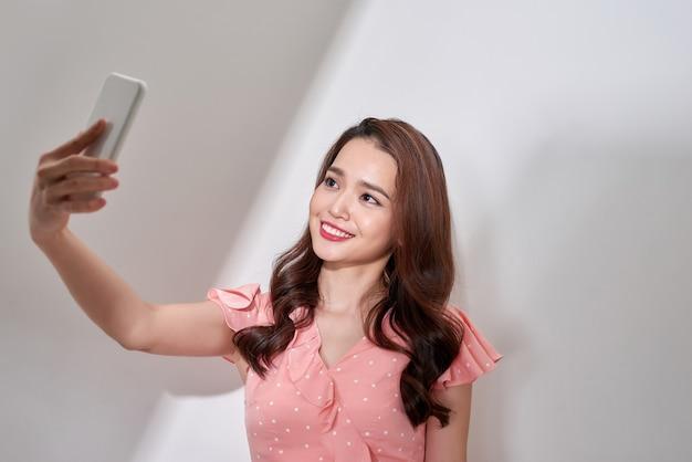 Asiatique souriante prenant un selfie avec un smartphone sur fond blanc