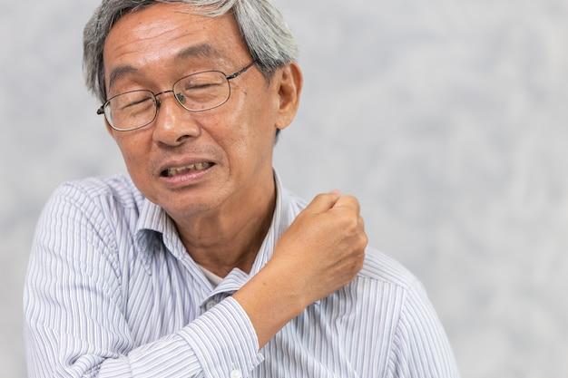 Asiatique sujet âgé douleur au cou et à l'épaule en utilisant la main pour masser et frotter la vue de face.