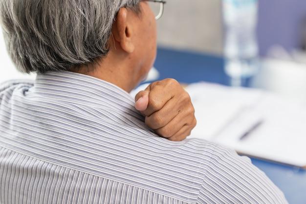 Asiatique sujet âgé douleur au cou et à l'épaule en utilisant la main pour masser et frotter.