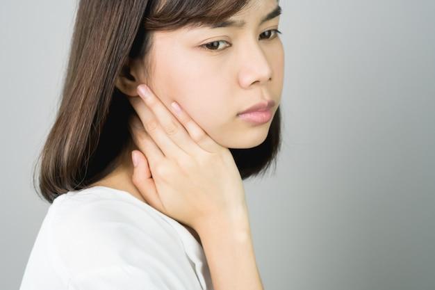 Une asiatique en tenue décontractée blanche attrape son épaule à cause de la douleur du travail acharné.