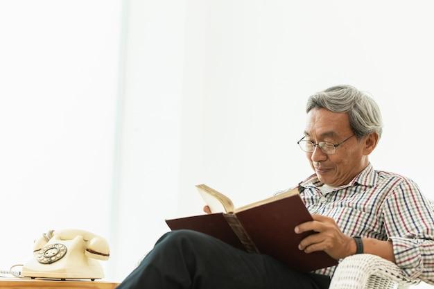 Asiatique vieil homme lunettes professeur assis sur la chaise, lecture de manuel avec copyspace