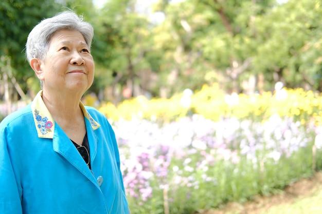 Asiatique vieille femme âgée femme âgée au repos reposant dans un jardin fleuri. mode de vie de loisirs senior