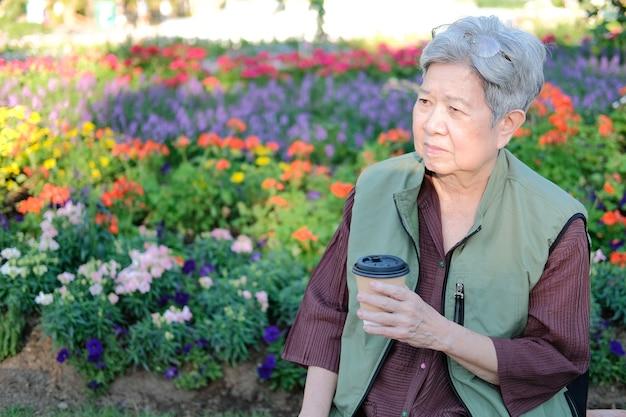 Asiatique vieille femme âgée femme âgée de boire du café thé dans le jardin. mode de vie de loisirs senior