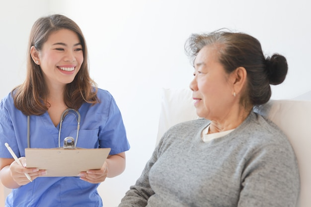 Asiatique vieille femme âgée sur le lit avec le médecin et son fils à l'hôpital