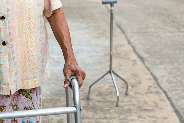 Asiatique vieille femme debout avec ses mains sur un bâton de marche