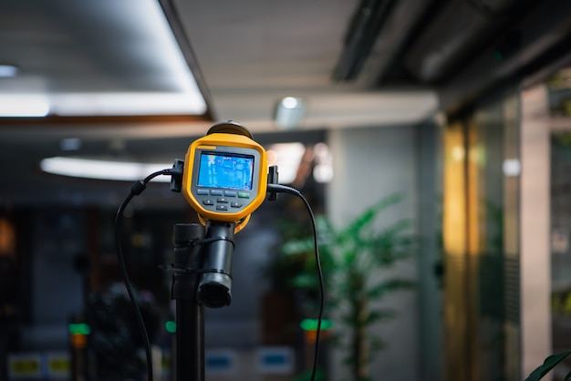 Les asiatiques attendent un contrôle de la température corporelle avant d'accéder au bâtiment pour contre la grippe épidémique covid19 ou la grippe à virus corona au bureau par thermoscan ou caméra thermique infrarouge