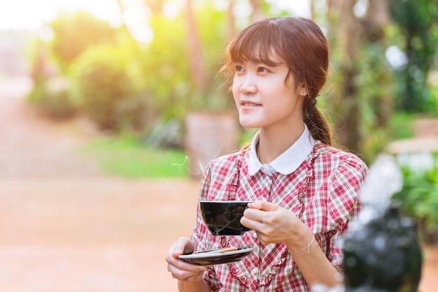 Asiatiques belles femmes avec une boisson chaude le matin avec fond de jardin parc