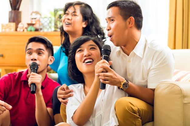 Asiatiques chantant lors d'une soirée karaoké et s'amusant