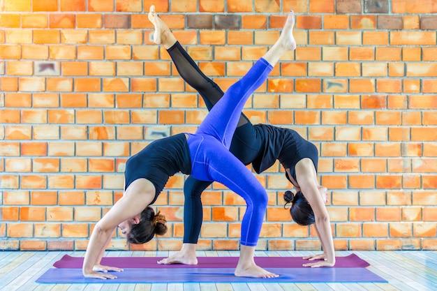 Asiatiques, deux, femme forte, pratique, yoga avancé, contre, a, mur, texturisé brun
