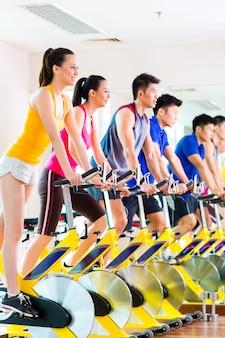 Asiatiques en formation de spinning à la salle de fitness